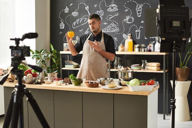 キッチンでブログを撮影している間、彼の手で新鮮なコショウを指しているエプロンの食品ブロガー