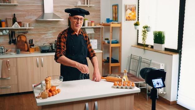 Продовольственный блогер готовит домашнюю выпечку перед камерой на кухне. блогер на пенсии, повар, влиятельный человек, используя интернет-технологии, общается и ведет блог в социальных сетях с помощью цифрового оборудования.