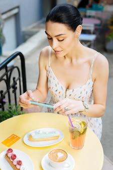 음식 블로거. 카페에 앉아 현대적인 스마트 폰을 들고 맛있는 디저트 사진을 찍는 꽤 인기있는 음식 블로거