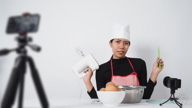 Продовольственный блогер в прямом эфире. шеф-повар женщины инструктора еды онлайн. готовим с абонентами через камеру телефона онлайн.