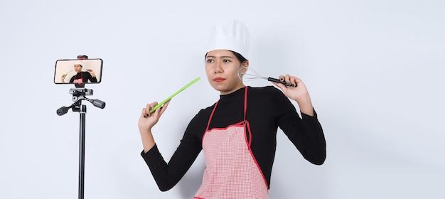 라이브 스트리밍하는 음식 블로거. 온라인 음식 강사 여자 요리사. 온라인 전화 카메라를 통해 구독자와 함께 요리합니다.