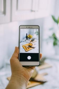 フードブロガーは、写真付きの携帯電話を持っているソーシャルネットワークの女性の手のためにスマートフォンで写真を撮ります