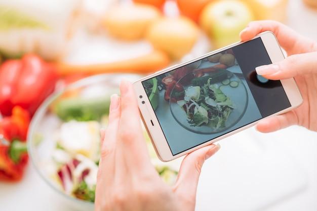 준비된 식사의 모바일 사진을 찍는 음식 블로거. 온라인 요리법과 건강한 라이프 스타일