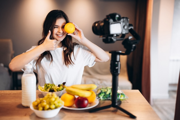 Food blogger young female cooking fresh vegan salad of fruits in kitchen studio, filming tutorial on camera for video channel. female influencer holds orange and talks about healthy eating.