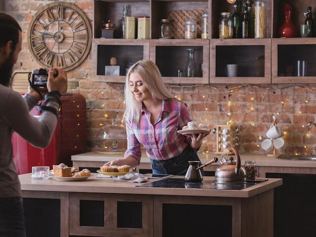음식 블로깅 사업. 커플 라이프 스타일. 신선한 수제 파이 구색을 가진 남자 촬영 여자.