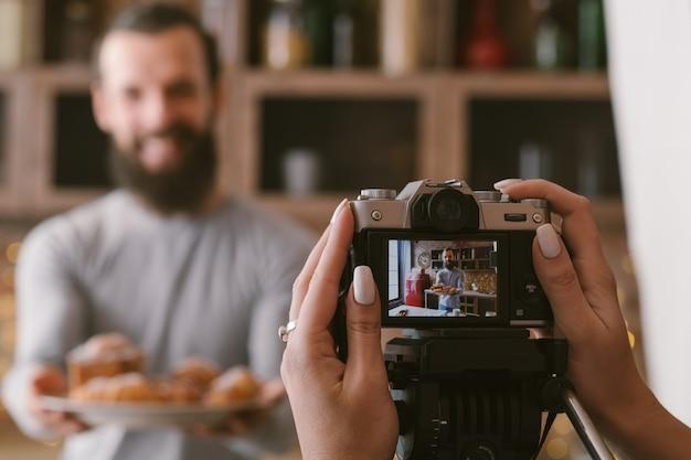 음식 블로깅 사업. 커플 라이프 스타일. 신선한 수 제 파이 구색을 가진 남자를 촬영하는 여자.