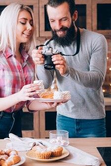 음식 블로그. 커플 라이프 스타일. 신선한 수제 케이크와 파이의 사진을 찍는 남자.