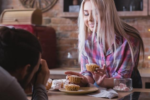 음식 블로그. 커플 라이프 스타일. 신선한 수제 머핀의 사진을 찍는 남자.