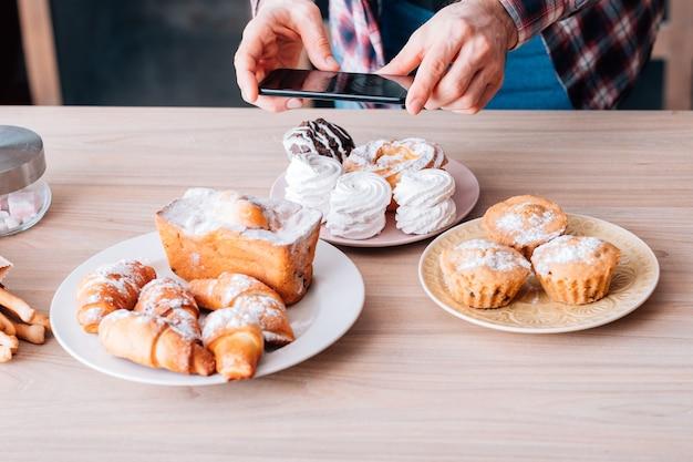 음식 블로깅 취미. 달콤한 수제 베이커리 구색. 모바일 사진. 신선한 케이크와 파이를 촬영하는 스마트 폰을 가진 남자.