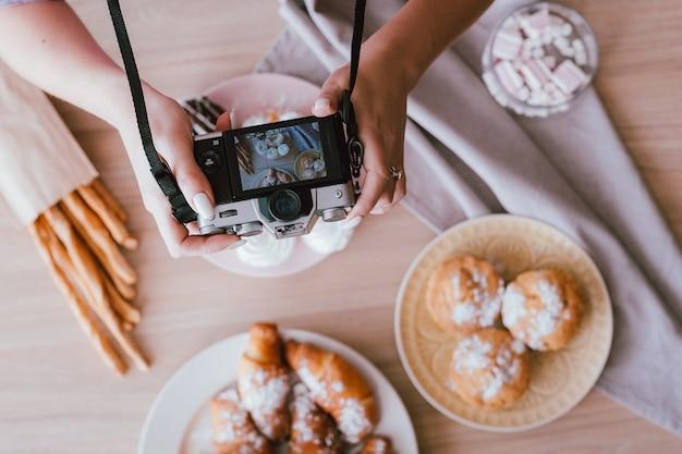 음식 블로깅 취미. 달콤한 수제 베이커리 구색. 위에서 신선한 케이크와 파이를 촬영하는 여자.