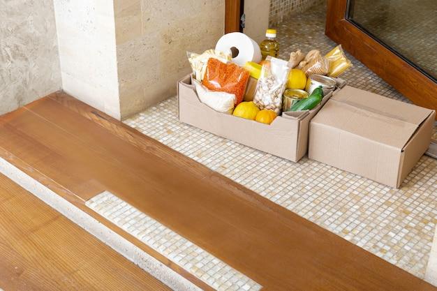 家のドアの近くの玄関先にフードボックスの配達。非接触型ソーシャル宅配、コロナウイルスのパンデミックでの安全なショッピング