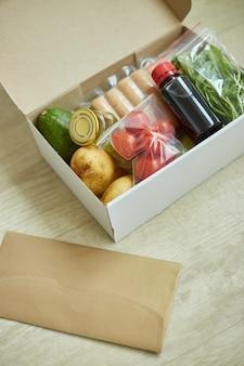 Еда в коробке из свежих ингредиентов и рецепт бланка заказа от компании по производству наборов еды, доставка, приготовление дома.