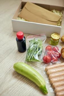 Набор еды в коробке из свежих ингредиентов и рецепт бланка заказа от компании по производству наборов еды, доставка, приготовление дома.