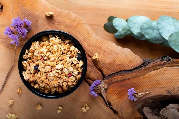 Концепция завтрака для еды органический мюсли или гранола на черной керамической чашке