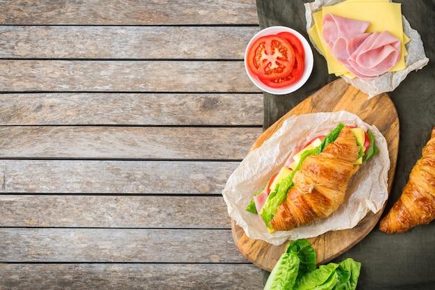 음식, 아침 식사, 아침 및 점심 식사, diy, 스스로 개념을 수행합니다. 나무 테이블에 재료, 햄, 치즈, 양상추, 토마토를 넣은 신선한 크루아상 샌드위치. 평면 위치, 복사 공간 배경