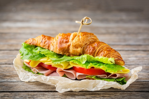 Food, breakfast, morning and lunch concept. fresh croissant sandwich with ham, cheese, lettuce and tomato on a wooden table