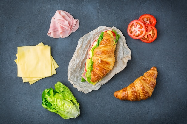 Food, breakfast, morning and lunch, diy, do it yourself concept. fresh croissant sandwich with ingredients, ham, cheese, lettuce and tomato on a table. flat lay background