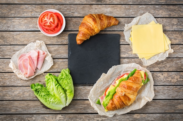 Food, breakfast, morning and lunch, diy, do it yourself concept. fresh croissant sandwich with ingredients, ham, cheese, lettuce and tomato on a wooden table. flat lay background