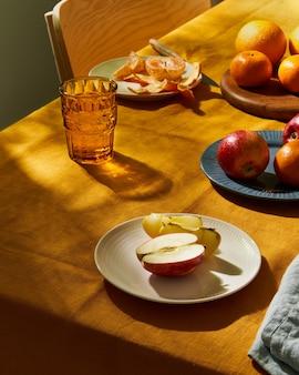 Еда для завтрака с фруктами на столе, накрытом ярко-желтой льняной скатертью, солнечный свет, глубокая жесткая тень