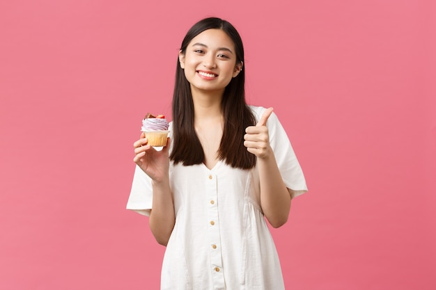 食品、カフェ、レストラン、夏のライフスタイルのコンセプト。デザートの素晴らしい味に満足している幸せなアジアの女性、パン屋からのおすすめのカップケーキ、立っているピンクの背景として親指を立てる。