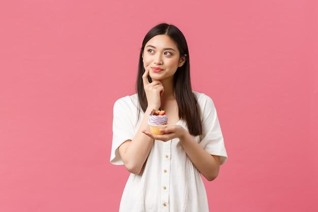 음식, 카페, 레스토랑, 여름 라이프스타일 컨셉입니다. 사려깊고 주저하는 아시아 여성이 의심스러운 시선을 피하고 칼로리를 다이어트를 유지하는 것으로 생각하고 맛있는 디저트를 먹고 싶어합니다.
