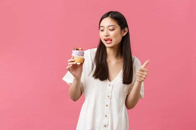 Cibo, caffè e ristoranti, concetto di stile di vita estivo. una cliente femminile sorridente e felice consiglia deliziosi cupcake allo spettacolo di prodotti da forno, mostrando il pollice in su e guardando il dessert con desiderio di mordere
