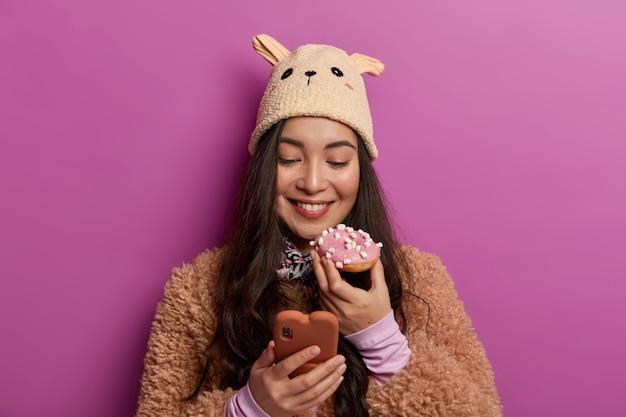 Concetto di cibo e calorie. felice ragazza millenaria morde la ciambella con appetito, chatta online tramite cellulare, si diverte a mangiare dolci