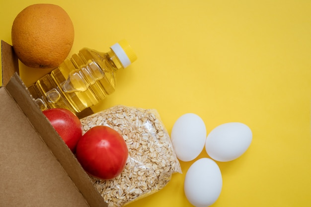 Food in a cardboard box on a yellow background