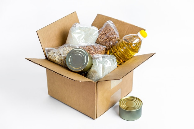 Food in cardboard donation box, isolated on white background. anti-crisis stock of essential goods for period of quarantine isolation. food delivery, coronavirus. the shortage of food.
