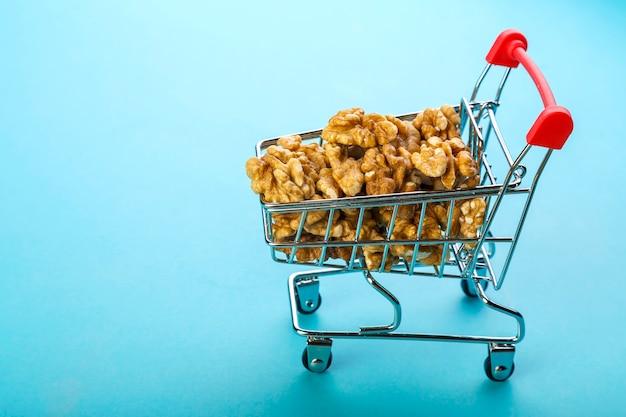 Продовольственная тележка заполнена очищенными грецкими орехами на синем фоне. копировать пространство горизонтальное фото