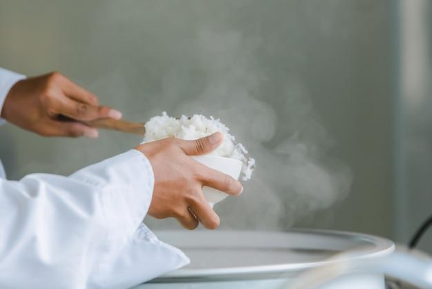 白いシェフの制服を着たフードシェフがホテルのレストランでお客様にご飯と料理を提供するためにキッチンでご飯をすくい取ろうとしています