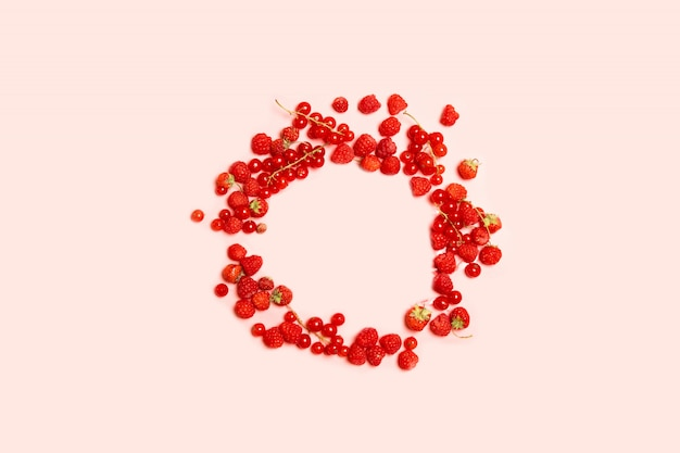 Food circle frame of red ripe currants, strawberries and raspberries
