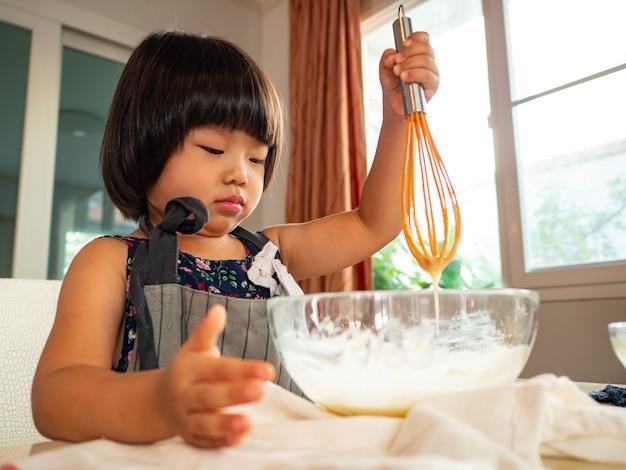 彼女の子供と一緒に台所の部屋で食品教室の家族。アジアの人々は家で一緒に活動をします。