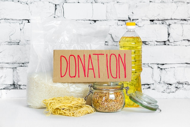 Food collection for donations, on a white brick background. anti-crisis stock of essential goods for the period of quarantine isolation. food delivery, coronavirus. the shortage of food.