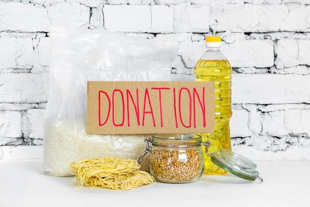 白いレンガの背景に、寄付のためのフードコレクション。検疫隔離期間中の必須商品の危機防止在庫。フードデリバリー、コロナウイルス。食糧不足。