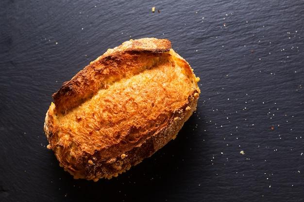 복사 공간이 있는 검은 배경에 있는 음식 개념 장인의 딱딱한 옥수수 빵