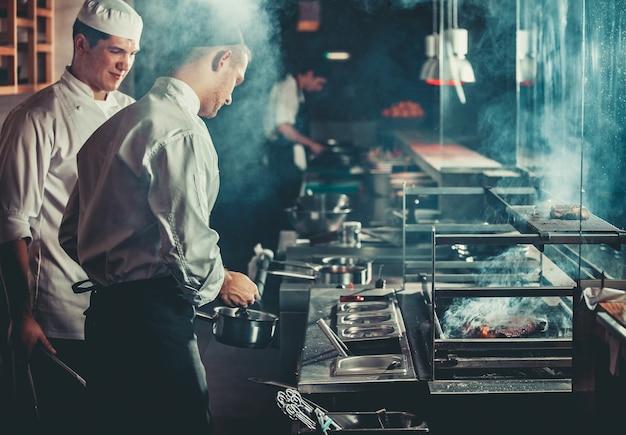 食品のコンセプト。白い制服を着たシェフが焙煎の程度を監視し、鍋に油を塗って肉に油をさします