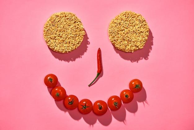 Концепция питания. лицо из острого перца чили, помидоров, лапши на розовом фоне