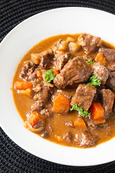 Food concept french classic beefs stew estouffade de boeuf in white ceramic plate with copy space