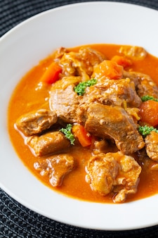 Food concept french classic veal stew marengo de veau in white ceramic plate with copy space
