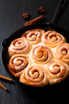 Food concept fresh baked homemade cinnamon rolls in skillet cast iron pan with copy space