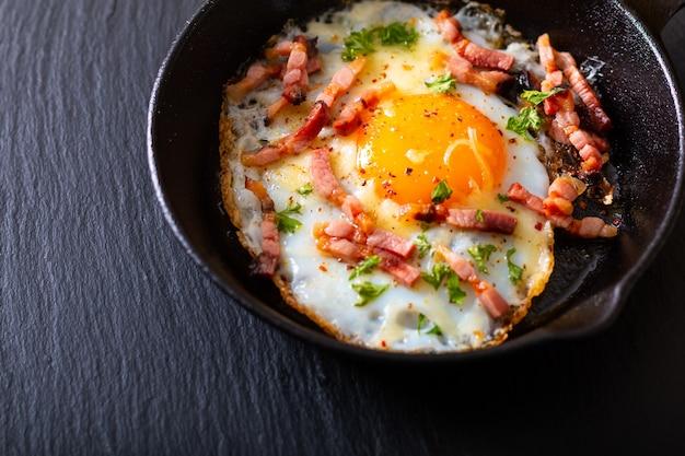 Концепция питания жареное яйцо и сырный бекон в сковородке чугуна с копией