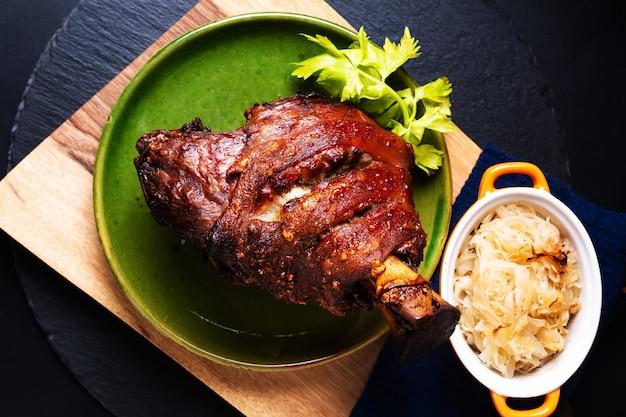 Продовольственная концепция немецкая свиная рулька или свиная рулька с квашеной капустой и рассолом на деревянной доске с копией пространства