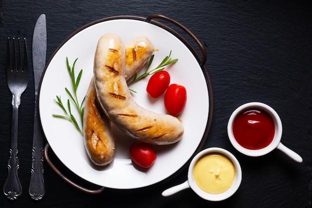 Продовольственная концепция барбекю на гриле белые сосиски на черном фоне с копией пространства