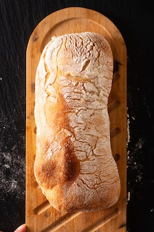 Food concept homemade artisan classic italian style yeast dough ciabatta bread on black slate board with copy space