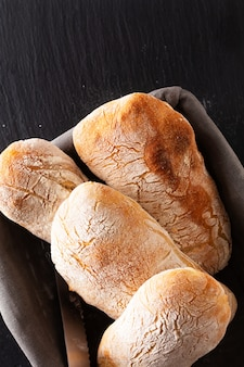 Food concept homemade artisan classic italian style yeast dough ciabatta bread on black slate board with copy space