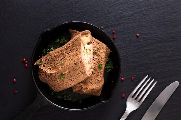 食品コンセプト自家製ハムとチーズクレープアイロンフライパンで黒いスレート背景
