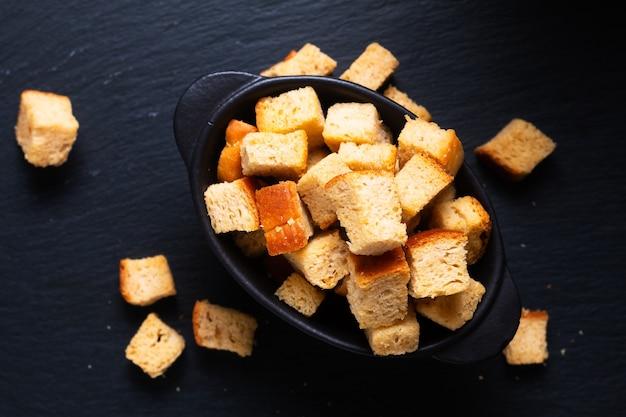 음식 개념 검은 배경에 복사 공간이 있는 홈메이드 유기농 크루통 빵