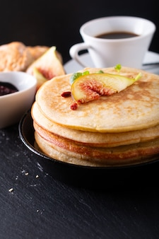 Food concept homemade organic pancakes stack with fig breakfast on black