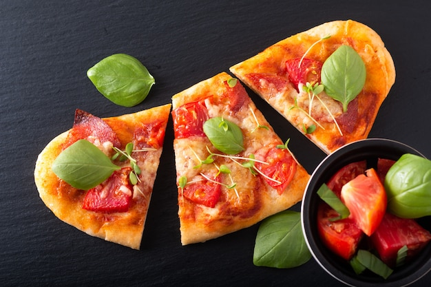 Food concept homemade organic pizza with tomato, basil and ham with copy space